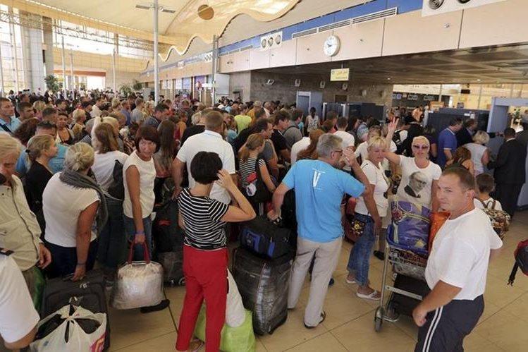 Decenas de turistas esperan en los mostradores del aeropuerto de Sharm el-Sheij (Egipto), el momento para poder partir a su hogar. (Foto Prensa Libre: EFE).
