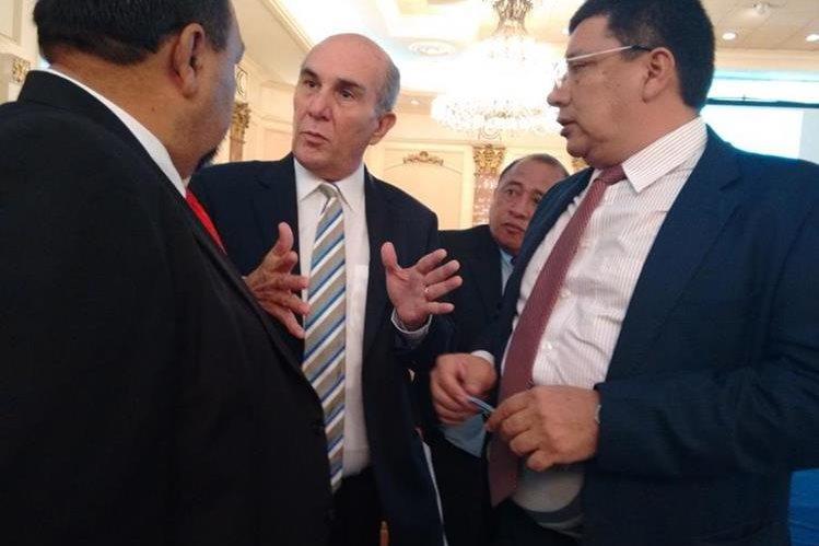 Los fiscales de los partidos UNE, Líder y UCN, discuten la posición del logotipo de su partido en la boleta electoral. (Foto Prensa Libre: M. Hernández)