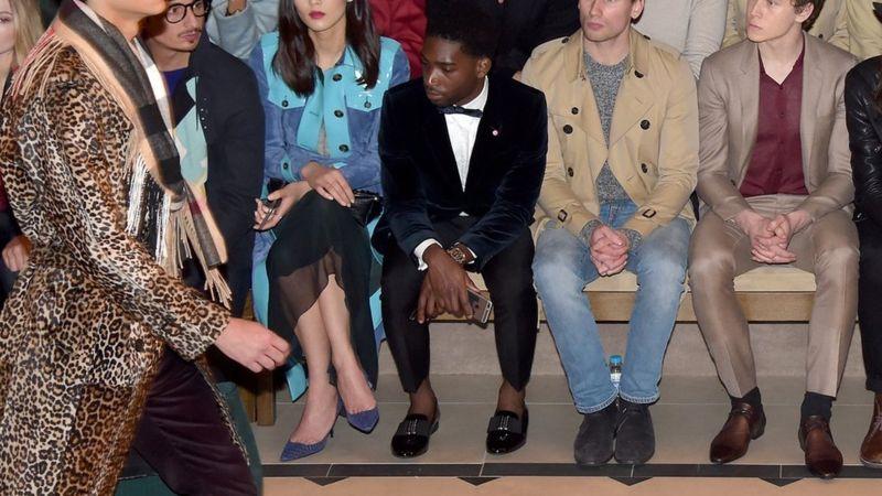 El cantante británico Tinie Tempah (centro), que ha ganado varios premios de estilo, mostrando sus tobillos en primera fila durante un desfile de moda de la London Fashion Week. (Getty Images).