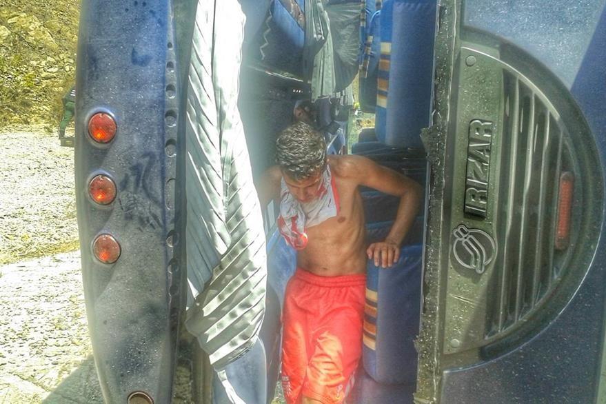 Un jugador del Huracán baja de los restos del autobús tras el accidente en el que bus perdió el control tras la falla de los frenos. (Foto Prensa Libre: AP)