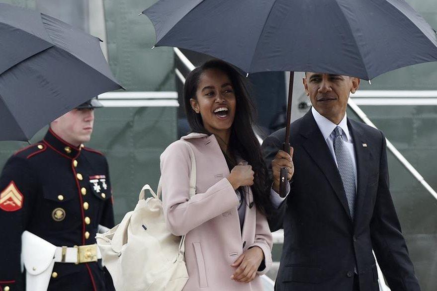 Barack Obama protege de la lluvia a su hija Malia durante su gira de trabajo. (Foto Prensa Libre: AP).