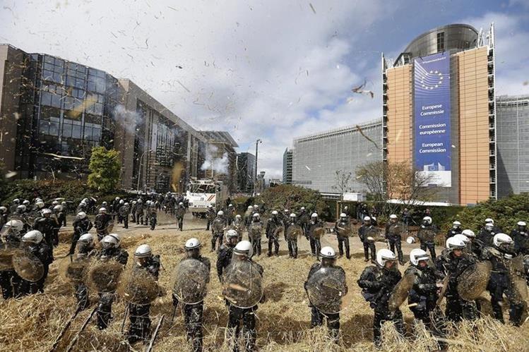 Policías protegen la sede de la Comisión Europea en Bruselas, ante protestas de agricultores efectuadas hoy. (PL-EFE)