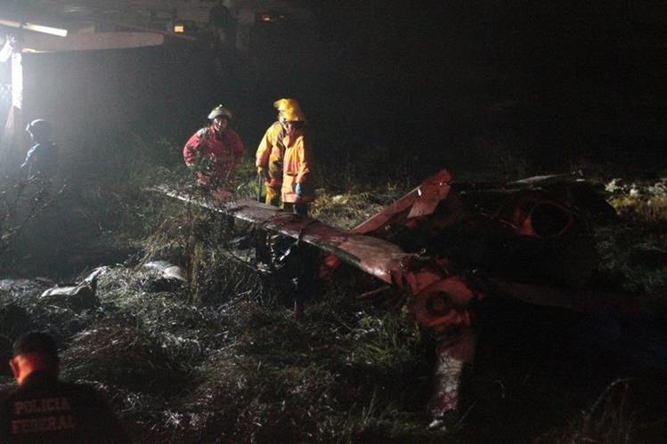 Bomberos rescatan los cuerpos de los dos tripulantes del helicóptero siniestrado. (Foto Prensa Libre: EFE).