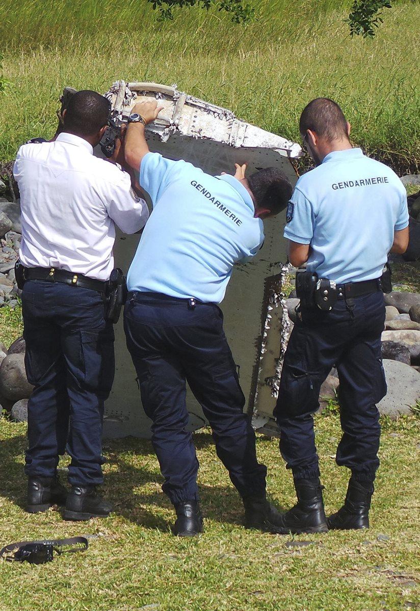 Oficiales en La Reunión inspeccionan el alerón encontrado la semana pasada. Después fue enviada a Francia. (Foto Prensa Libre: EFE).