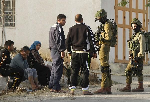 Soldados israelíes bloquean el ingreso de palestinos a raíz del atentado en Tel Aviv.