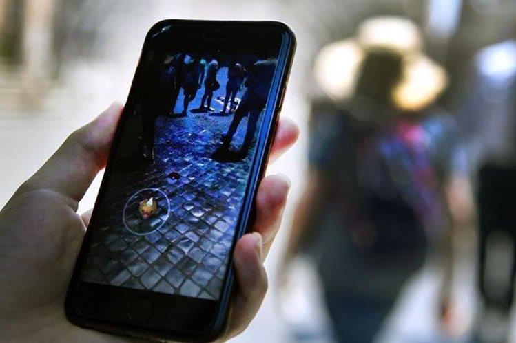 Una mujer sostiene su teléfono mientras juega Pokémon Go. (Foto Prensa Libre: AFP).