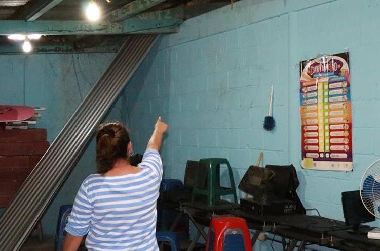 Una maestra del instituto muestra el área donde presumen ingresaron los malhechores. (Foto Prensa Libre: Cristian Icó)