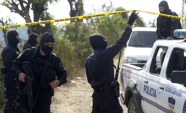 Efectivos de la PNC se encuentran en la escena del crimen donde murieron dos personas por las pandillas. (AFP).