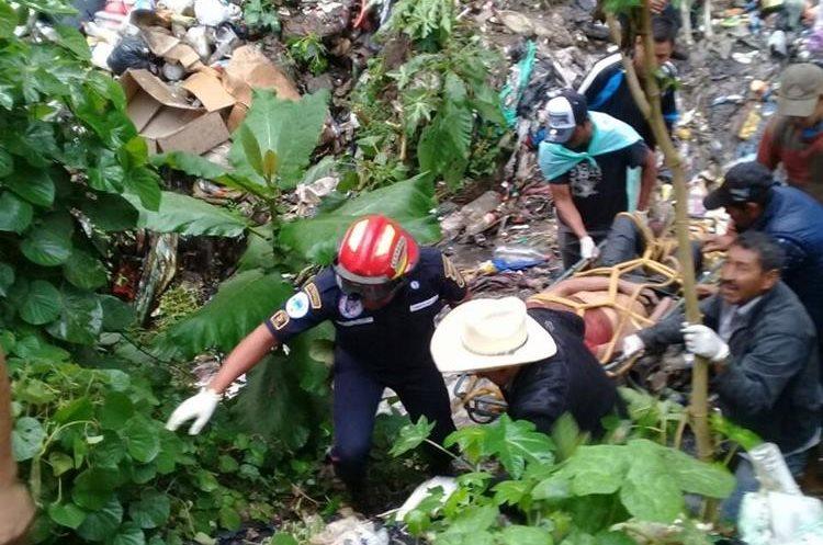 Recolectores ayudan a los socorristas a rescatar el el cadáver. (Foto Prensa Libre: Víctor Chamalé)