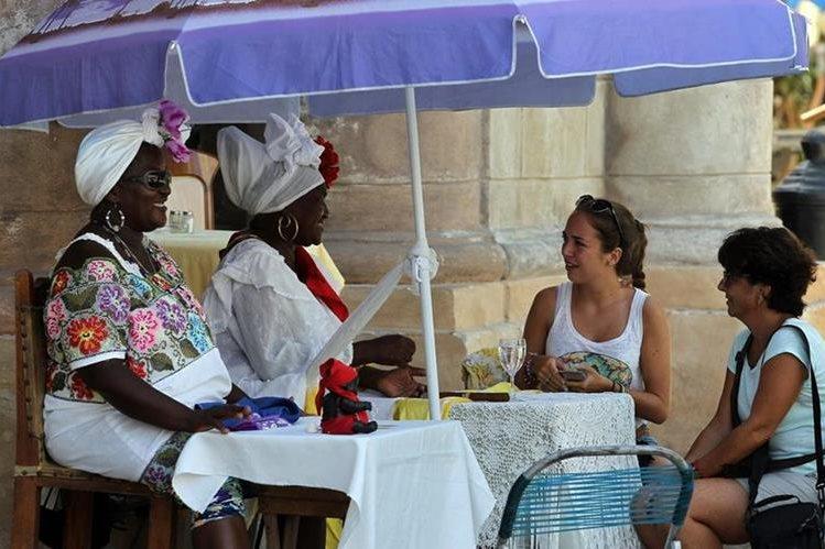 <em>Dos turistas consultan su futuro con cartománticas en La Habana, Cuban. (Foto Prensa Libre: EFE).</em>