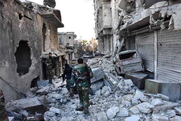 Fuerzas progubernamentales caminan en medio de la destrucción en un barrio de en Alepo. (AFP).