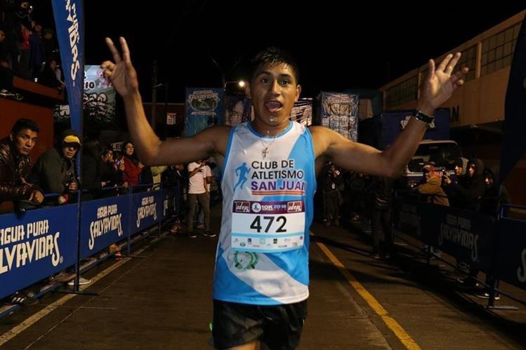 Carlos Ávila Raxón alza los brazos al cruzar la meta en los 10K nocturnos de Quetzaltenango. (Foto Prensa Libre: Raúl Juárez)
