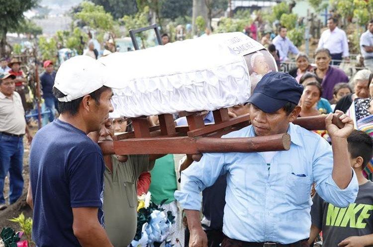 Familiares de las víctimas introducen en la fosa común el ataúd que guarda los restos de Silvia Isabel Sánchez. (Foto Prensa Libre: Julio Sicán)