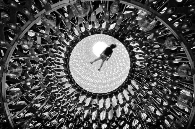 """El Hive es la nueva y espectacular escultura inspirada en un panal y que se puede ver en el jardín botánico de Londres, Kew Gardens. Naf Selmani lo retrató desde abajo, mientras uno de los visitantes reposaba en la parte superior, sobre una superficie de cristal. """"Esta multisensorial experiencia integra arte, ciencia, paisaje y arquitectura"""", dice el fotógrafo. NAF SELMANI"""