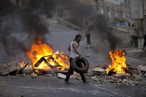 Un palestino coloca una llanta a una barricada durante los enfrentamientos.