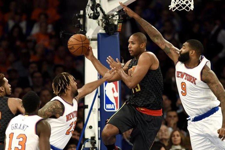 El jugador Al Horford de los Hawks intenta un lanzamiento ante Kyle O'Quinn (d), Derrick Williams (3-i), y Jerian Grant (2-i) de los Knicks. (Foto Prensa Libre: EFE)