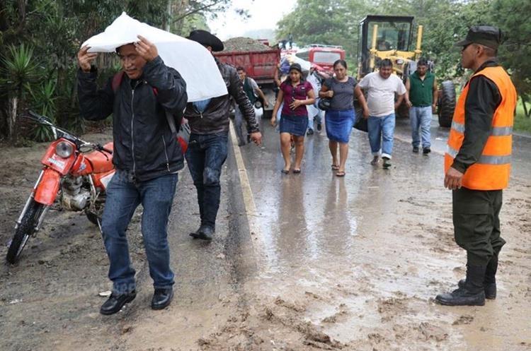 El hundimiento en el km 240 de la ruta Interamericana dejó incomunicados a Quetzaltenango y Huehuetenango, pobladores se las ingenian para trasladarse a sus destinos. (Foto Prensa Libre: Mike Castillo)