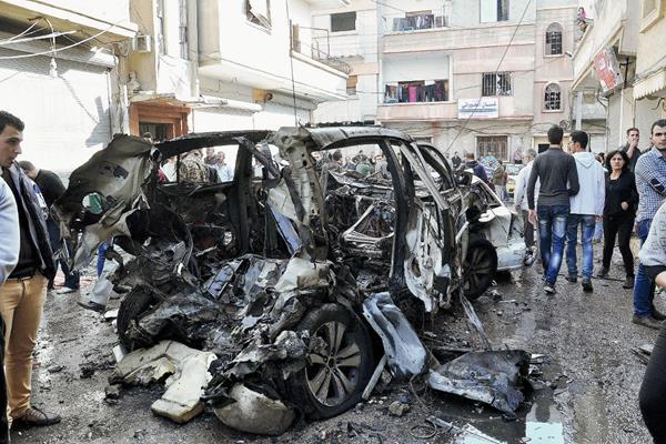 Policías y ciudadanos sirios observan los daños por el bombardeo. (Foto Prensa Libre:EFE).