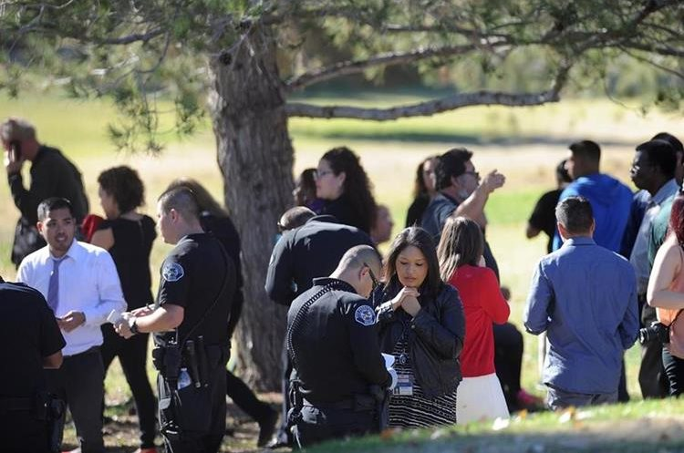 People gather at San Bernardino Golf Course after being evacuated from the scene of a shooting in San Bernardino, Calif. on Wednesday, Dec. 2, 2015. Police responded to reports of an active shooter at a social services facility.   (Micah Escamilla/Los Angeles News Group via AP)