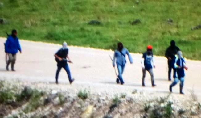Un grupo de manifestantes camina en la carretera principal de Ixquisis, algunos portan armas de fuego. (Foto Prensa Libre).