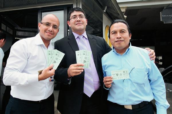 Tres aficionados posan orgullosos con sus entradas para el juego de mañana por la noche. (Foto Prensa Libre: Marcela Morales)