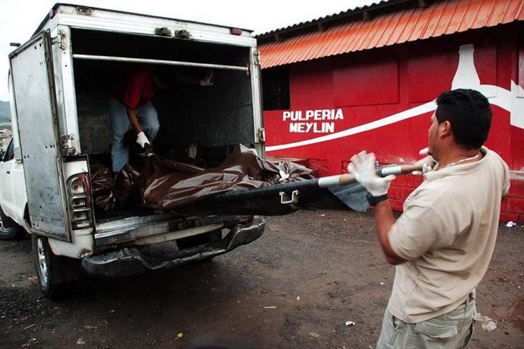 Especialistas trasladan los cadávers de los jóvenes asesinados en Honduras. (Foto Prensa Libre: AFP)