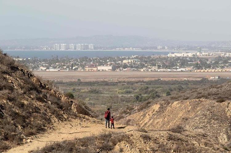 Un hombre y un niño fueron captados antes de cruzar de forma ilegal a los Estados Unidos, fotografiados desde Tiajuana.