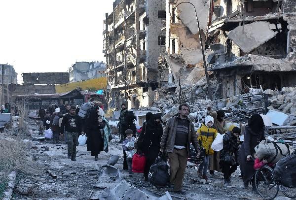 Sirios huyen de los bombardeos en Alepo después de que la tropa del régimen retomara el área de los rebeldes.(AFP).