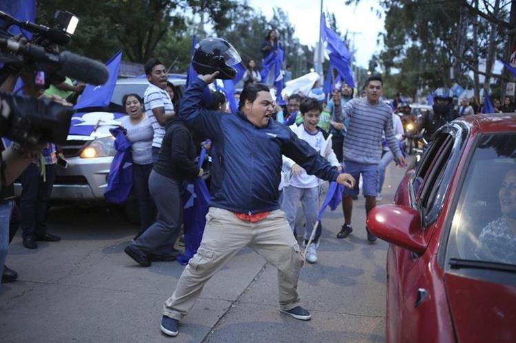 Simpatizantes del Partido Nacional de Honduras le arrebatan una bandera de la Alianza contra la Corrupción a personas que conducían en un vehículo durante una manifestación en Tegucigalpa. (Foto Prensa Libre: EFE)