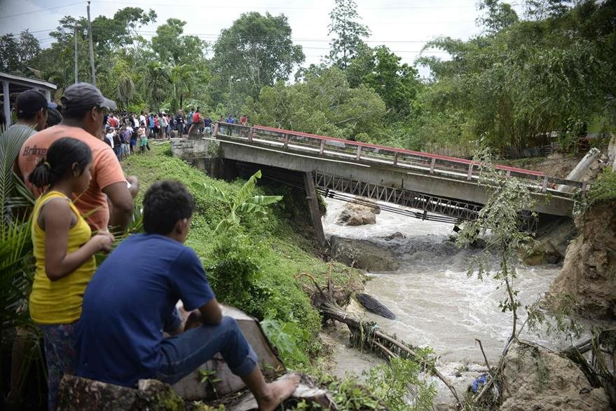 Un grupo de personas observa la destrucción del puente El Arroyito.(Foto Prensa Libre: AFP)