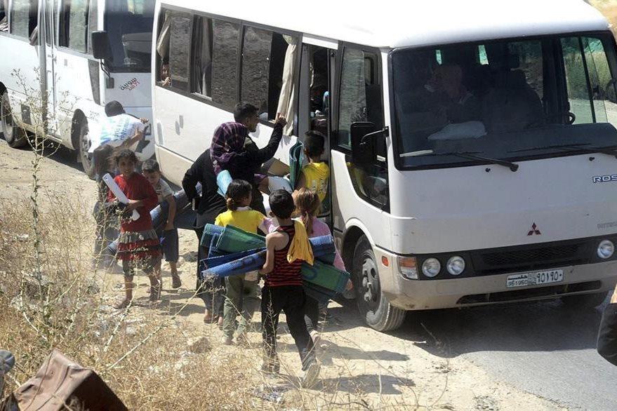 Mujeres y niños abordan un autobús dejar Alepo, una de las ciudades más golpeadas por el conflicto bélico en Siria. (Foto Prensa Libre: EFE).