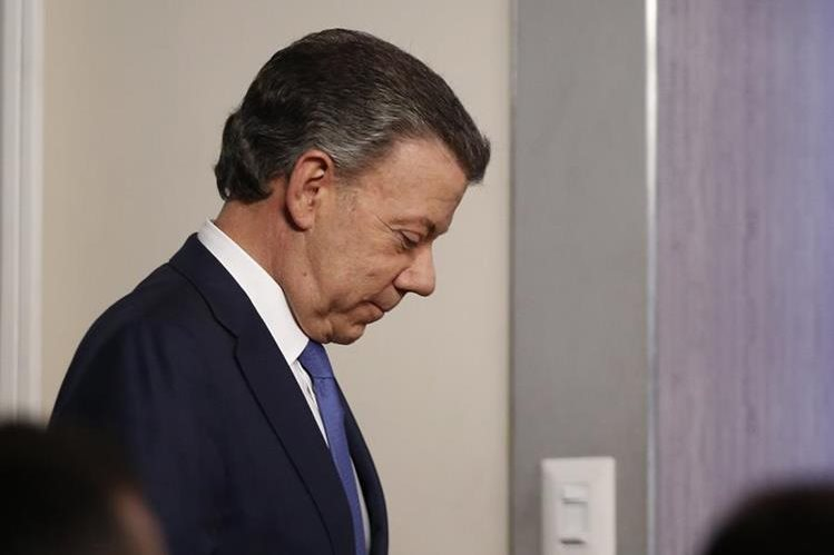 El presidente de Colombia, Juan Manuel Santos, se retira de la conferencia de prensa luego de reunirse con el expresidente Uribe. (Foto Prensa Libre: AP)