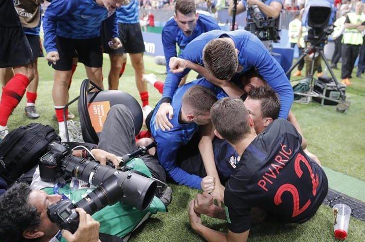 Al ver el choque los compañeros de Cortez toman fotos de la celebración croata.