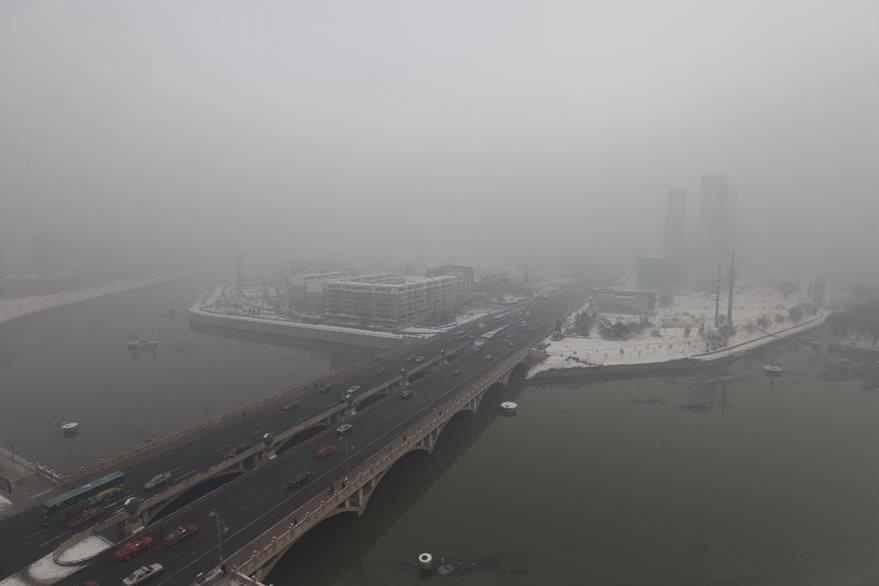 Bloque residencial cubierto de humo contaminante en Jilin, China. (Foto Prensa Libre: AFP).