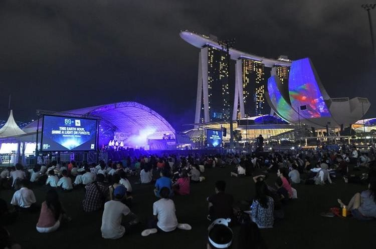 People gather at the Floats next to Marina Bay Sands hotel and resort before lights are switched off during the Earth Hour campaign in Singapore on March 19, 2016. Millions of people from 178 countries and territories are expected to take part in WWF