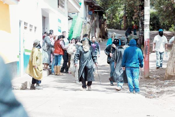 Los encapuchados retienen a dos personas dentro de un centro educativo. (Foto Prensa Libre: Estuardo Paredes)