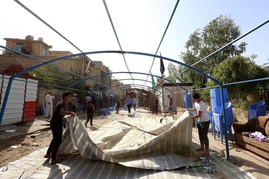 Iraquíes remueven objetos en zona del ataque suicida. (AFP)