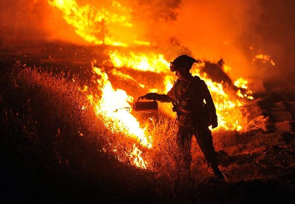 <em>Bomberos trabajan para controlar el incendio forestal.</em>
