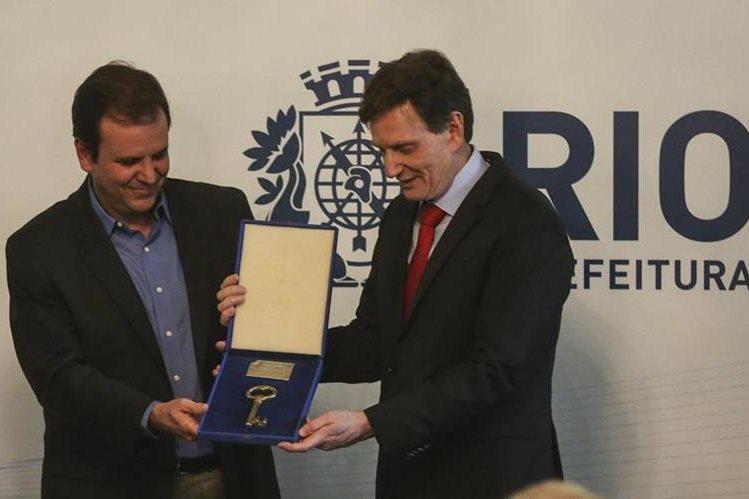 El ex alcalde de Río de Janeiro, Euardo Paes, entrega la llave de la ciudad al senador Marcelo Crivella quien asumió como alcalde de Río de Janeiro. (Foto Prensa Libre: EFE)
