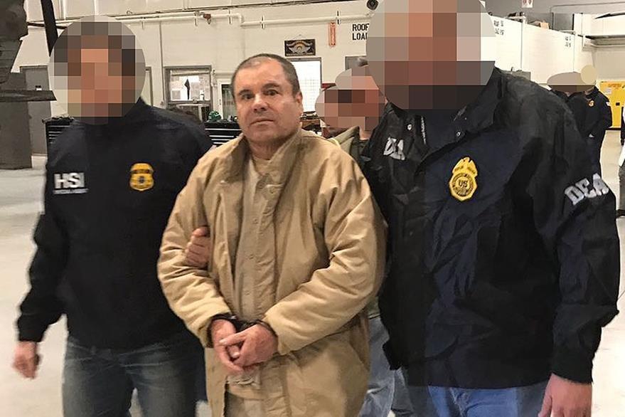 """Joaquin Guzman """"el Chapo"""" Guzmán (c) es escoltado por dos policías en Ciudad Juarez. (AFP)."""