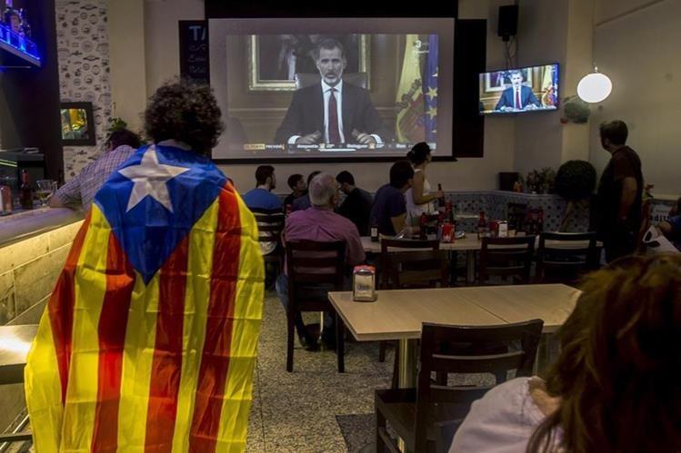 Varias personas miran el discurso del Rey Felipe VI durante la jornada de paro general en España. (Foto Prensa Libre: EFE)