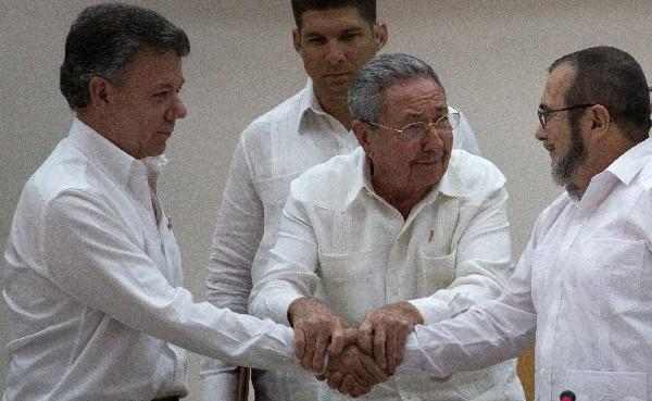 Raúl Castro, centro, apoya a Juan Manuel Santos, -izq-, y el comandante de las Farc, Timoleón Jiménez que se dan la mano, en La Habana, Cuba.