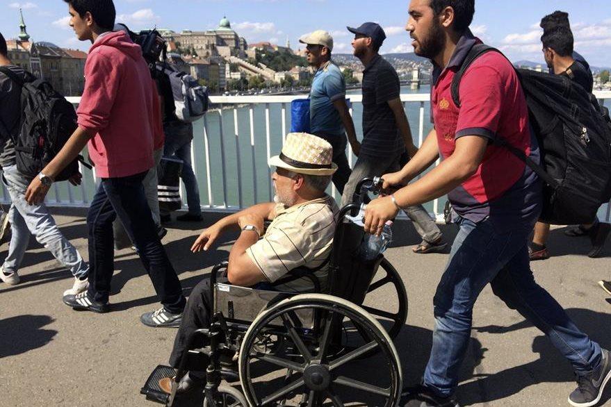 En silla de ruedas un migrante atraviesa Budapest en busca de la frontera con Austria. (Foto Prensa Libre: AP).