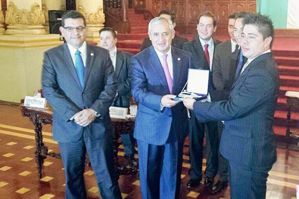 El Presidente Otto Pérez entregó la medalla a Luis rodríguez, representante de Guateambiente. (Foto Prensa Libre: Jessica Gramajo)