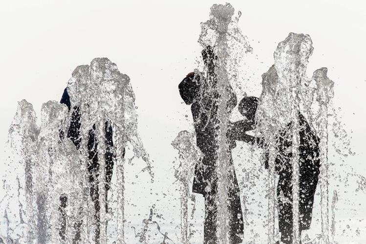 Varias personas se refrescan en una fuente para combatir el calor en el puerto de Evian, Francia.(Foto Prensa Libre:EFE9.