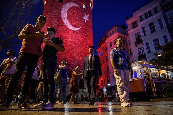 Varias personas se toman fotos cerca de la Torre de Gálata, en Estambul. (Foto Prensa Libre:AFP).