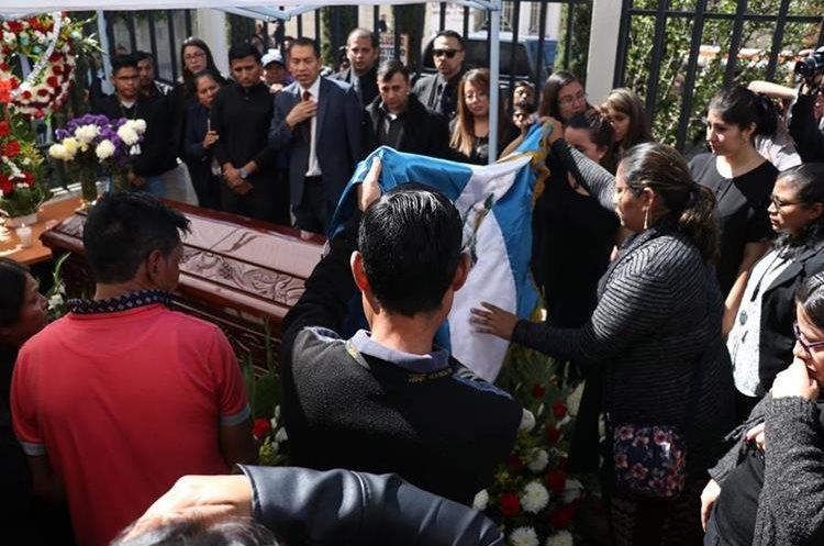 Compañeros de trabajo colocan bandera de Guatemala sobre el féretro de la víctima