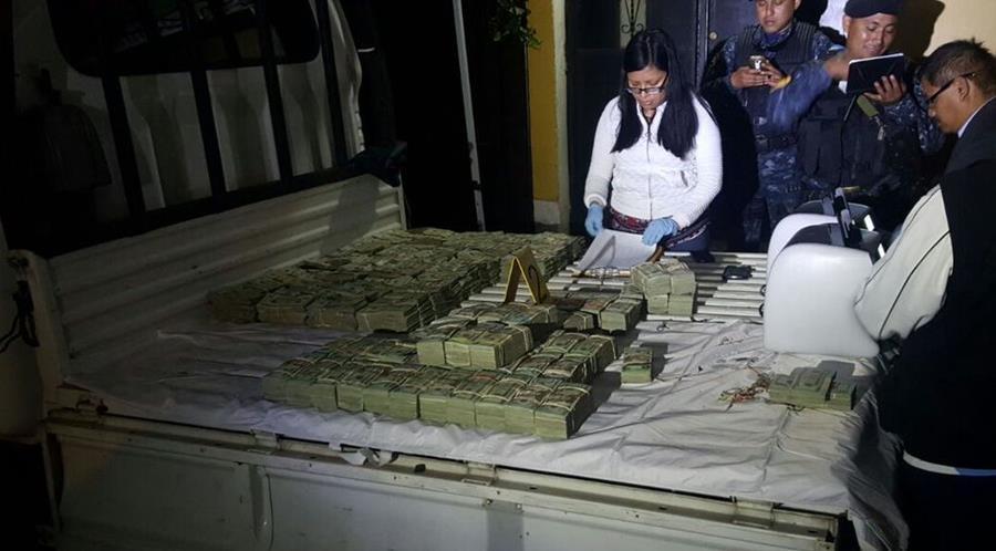 Fiscales contabilizan el dinero encontrado en una caleta dentro de un camión. (Foto Prensa Libre: PNC)