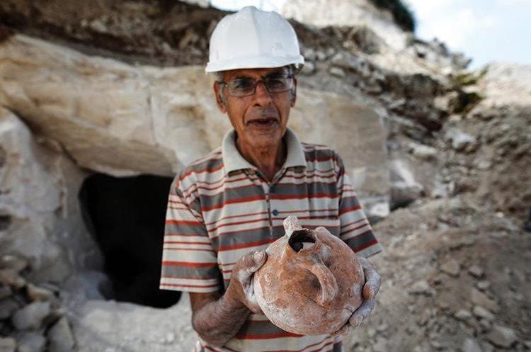 Un arqueólogo muestra un tipo de vasija hallado en excavación. (Foto Prensa Libre: AFP)