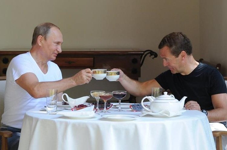 Russian President Vladimir Putin, left, and Prime Minister Dmitry Medvedev jokingly toast having a lunch during their meeting at the Black Sea resort of Sochi, Russia, Sunday, Aug. 30, 2015. (AP Photo/RIA Novosti, Mikhail Klimentyev, Presidential Press Service)